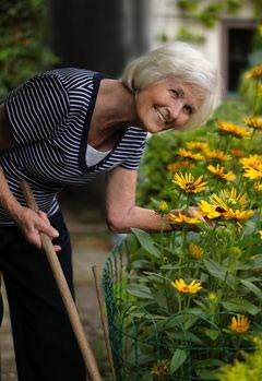 senior woman working in flower garden and smiling